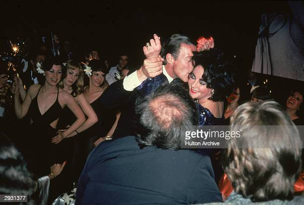 American fashion designer Halston kisses teh cheek of British-born actor Elizabeth Taylor at a fundraiser for the Martha Graham Dance Company, circa...