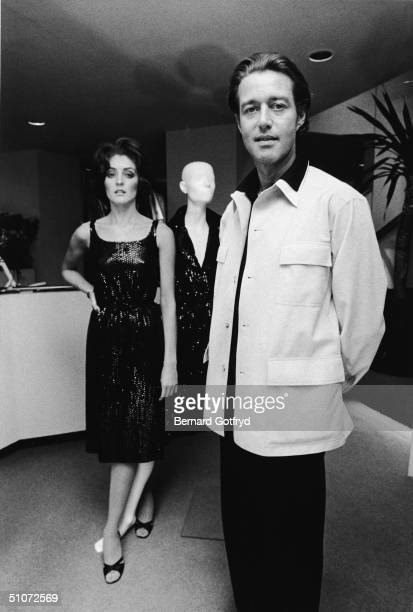 American fashion designer Halston poses with an unidentified model whose legs are entwinned with those of a mannequin, 1968.