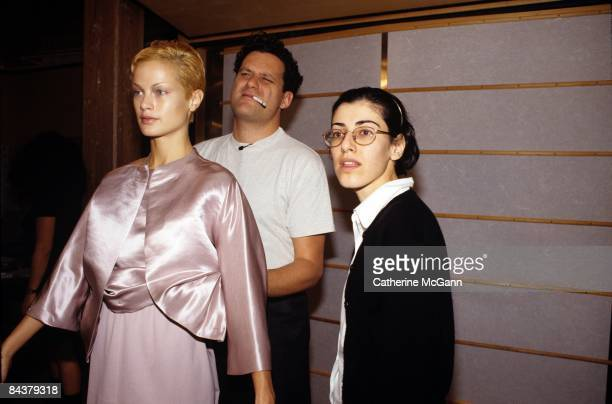 American fashion designer Isaac Mizrahi , looks in the mirror and squints while adjusting an outfit of his design worn by American model Carolyn...