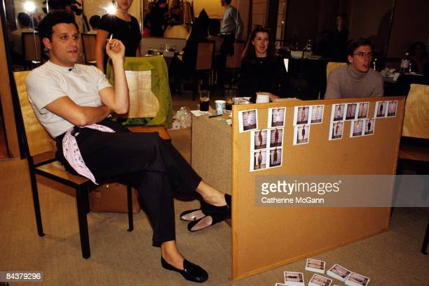 American fashion designer Isaac Mizrahi smokes while viewing a model out of frame wearing one of his latest designs on October 30, 1995 in his...