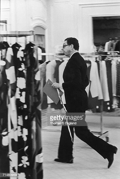 American fashion designer James Galanos walks past racks of clothing in a Saks Fifth Avenue department store a notepad and a tape measure in his hand...