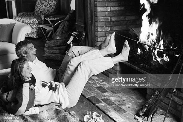 American fashion designer Ralph Lauren and his wife therapist Ricky Lauren share a laugh as they warm their feet at the fireplace in their home East...