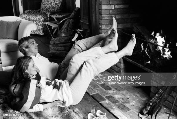American fashion designer Ralph Lauren and his wife therapist Ricky Lauren warm their feet at the fireplace in their home East Hampton New York...