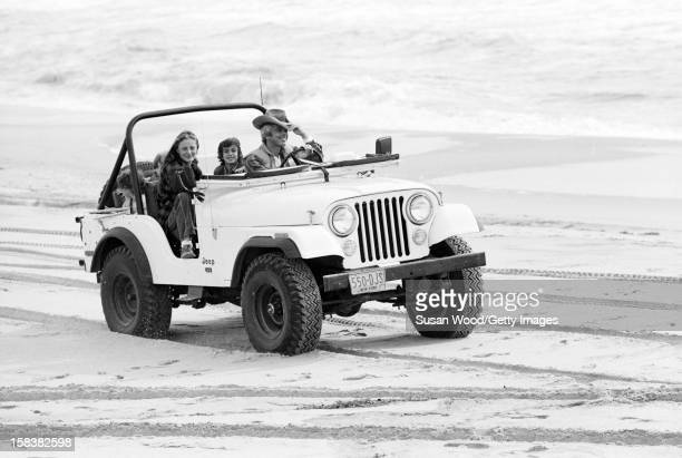 American fashion designer Ralph Lauren and his wife, therapist Ricky Lauren, drive in a jeep on the beach with their children, David, Andrew, &...