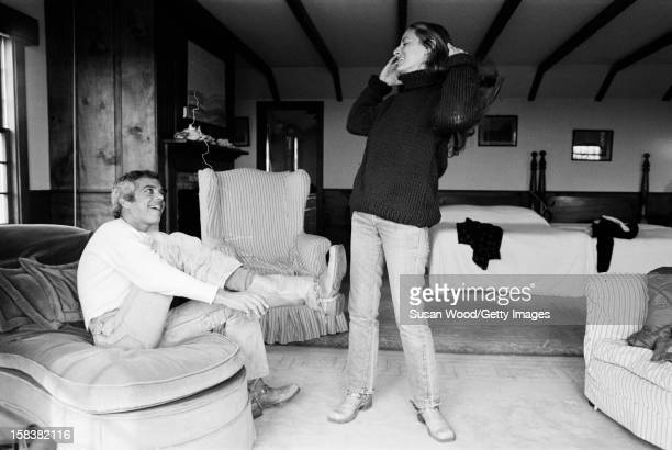 American fashion designer Ralph Lauren laughs with his wife therapist Ricky as he puts on a pair of cowboy boots in the bedroom of their home East...