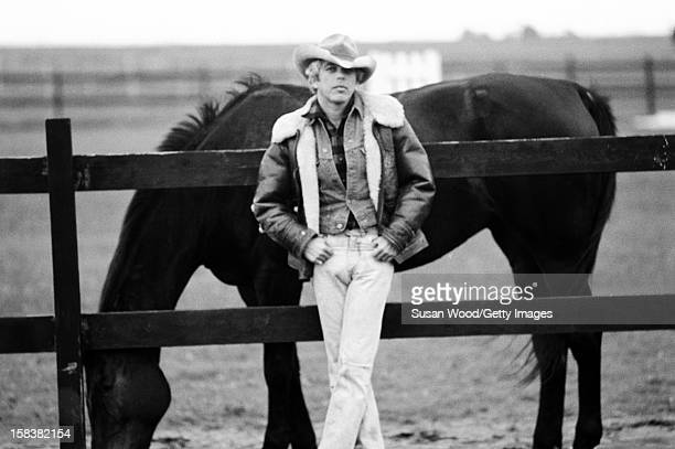 American fashion designer Ralph Lauren poses beside a horse near his home East Hampton in November 1977