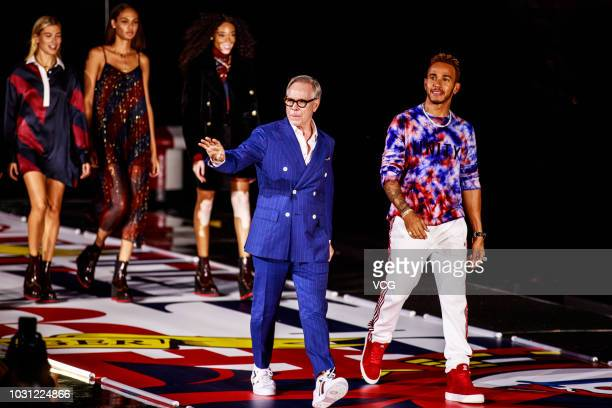 American fashion designer Tommy Hilfiger of Tommy Hilfiger Corporation and British racing driver Lewis Hamilton walk the runway during the Tommy...