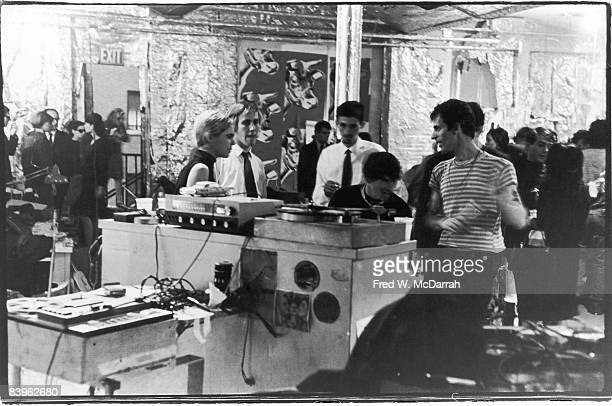 American fashion model and actress Edie Sedgwick and photographer Billy Name stand with unidentified others on either side of the dj 'booth' during a...