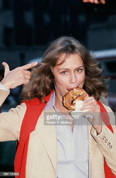 American fashion model and actress Lauren Hutton points to her head as she eats a pretzel on a street in Manhattan New York New York April 1977