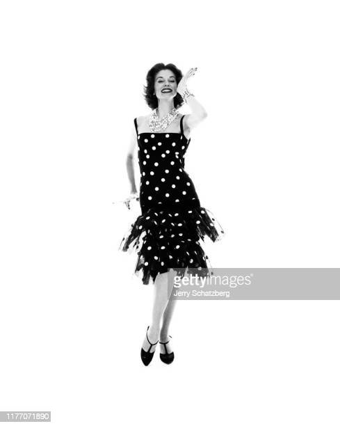 American fashion model and actress Suzy Parker in a polka dot dress dances against a white background New York New York February 17 1958 The photo...