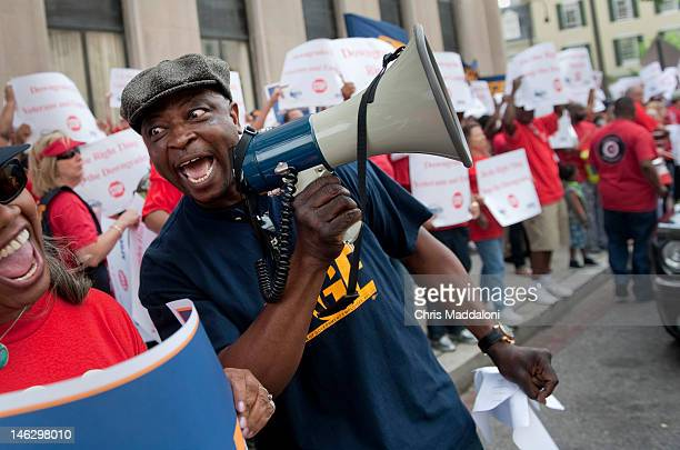 American Federation of Government Employees union member Rotimi Onaghise leads a rally in front of the Veterans Affairs building to 'show support for...