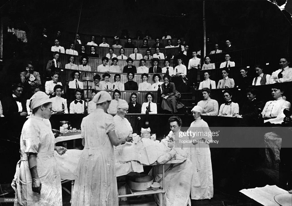 American female doctors in an operating theatre being watched by students.