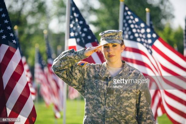 American female soldier saluting in a Field of American Flags
