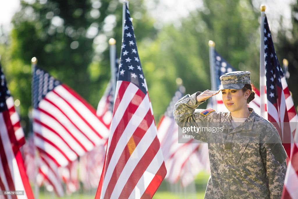 American Female Soldier saluting in front of American Flags : Stock Photo