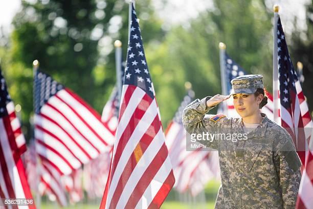 American hembra soldado todos saludamos en frente de Banderas americanas