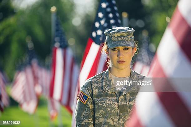 American Female Soldier standing in front of American Flags