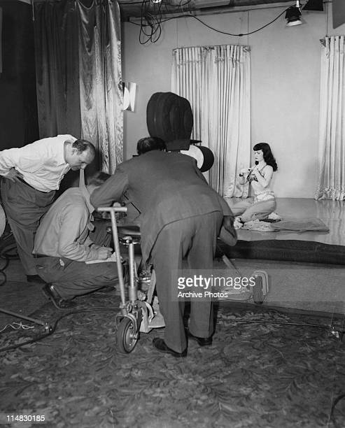 American fetish photographer and filmmaker Irving Klaw confers with his camera crew during the filming of a harem dance sequence with model Bettie...