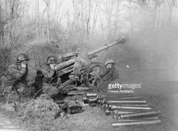 American field artillerymen of the United States 7th Army use a captured German Wehrmacht 75mm Pak 40 anti-tank gun to fire upon positions of the...