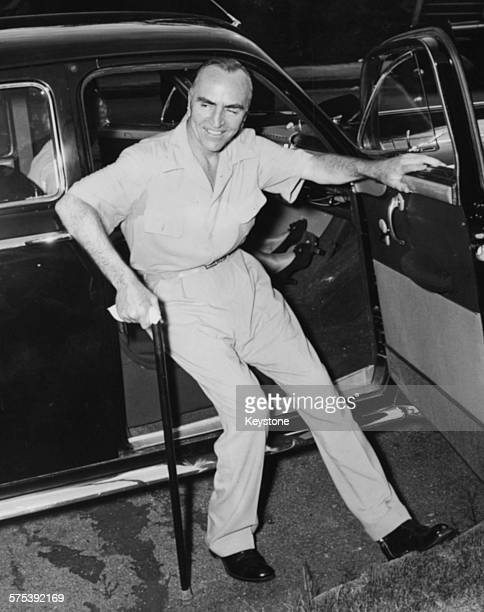 American fighter ace Captain Eddie Rickenbacker pictured using a cane to help him get out a car for his injuries sustained following a near fatal...