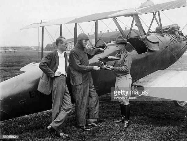 American fighter pilot Eddie Rickenbacker leans against a Curtiss Oriole as he receives a model of a Curtiss racer plane from Colonel Benjamin D...