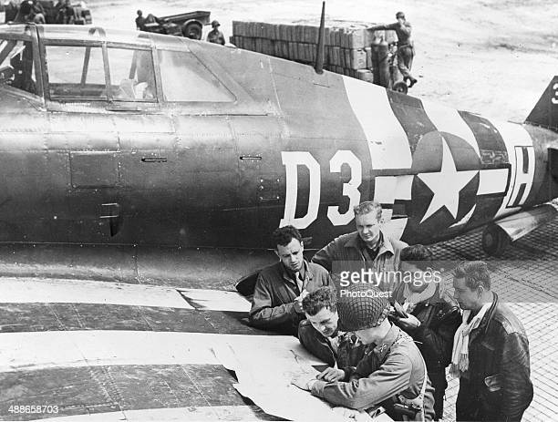 American fighter pilots plot a course for another operation against German military installations in France tracing the route on a map stretched on...