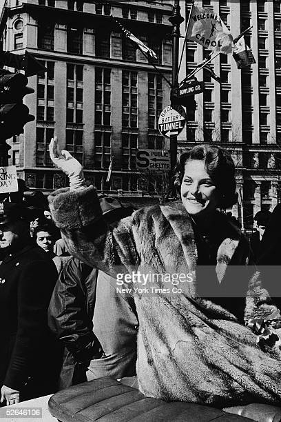 American figure skater Carol Heiss dressed in a fur coat and white gloves waves from the back of a car during a ticker tape parade in her honor New...