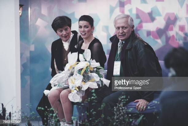 American figure skater Nancy Kerrigan of the United States team pictured with a bouquet of flowers and coaching staff after completing her routine...