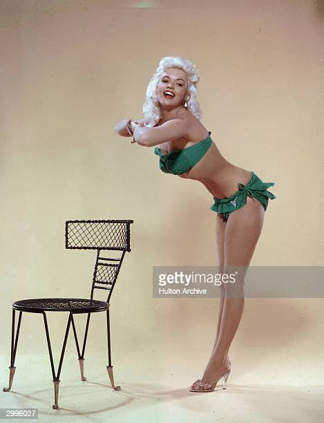 American film actor and sex symbol Jayne Mansfield leans forward from the waist and clasps her hands together in a studio portrait mid 1950's She...