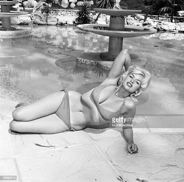 American film actor and sex symbol Jayne Mansfield lounges provocatively in a bikini near a pool mid 1950's