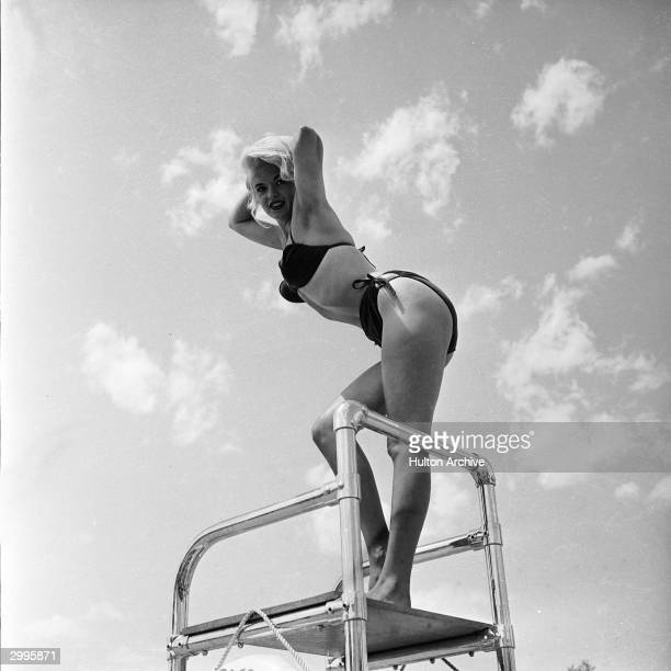 American film actor and sex symbol Jayne Mansfield poses in a bikini atop a lifeguard chair at the Dunes Hotel Las Vegas Nevada mid 1950's She leans...