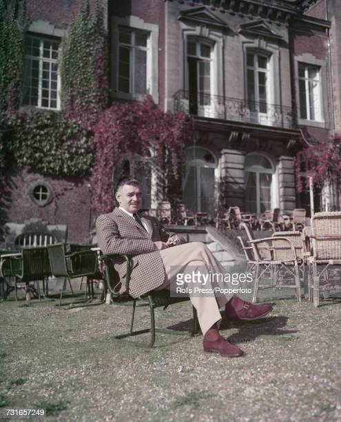 American film actor Clark Gable pictured sitting in a garden chair outside a villa in Klosterneuburg Austria circa 1959