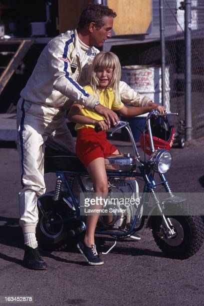 American film actor Paul Newman helps his daughter Elinor on a motorbike during the filming of 'Winning' Los Angeles California 1969