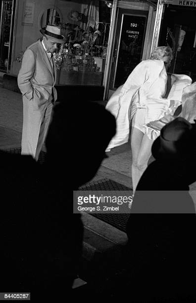 American film actor Tom Ewell stands with his hands in his pockets as he watches actress and sex symbol Marilyn Monroe on location during the filming...