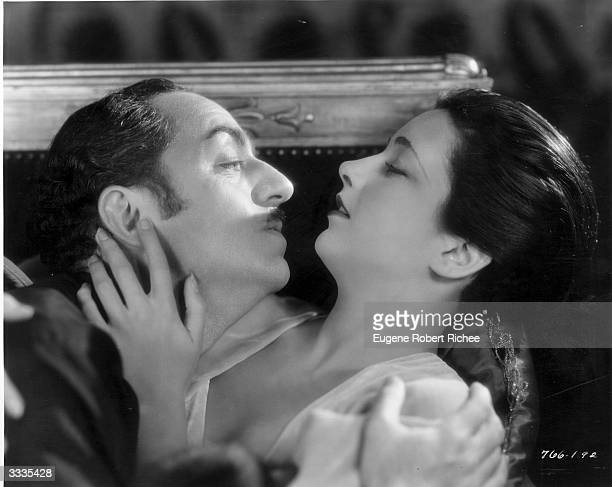 American film actor William Powell makes romantic advances towards actress Kay Francis in a scene from the Paramount film 'Behind the MakeUp'...