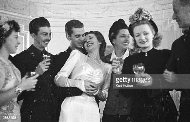 American film actress Carole Landis with her husband American Airforce captain Thomas Wallace receiving a toast from guests at their wedding...