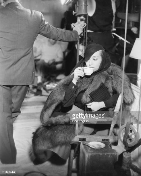 American film actress Carole Lombard breaks for refreshments during the filming of the comedy film 'The Princess Comes Across' directed by William K...