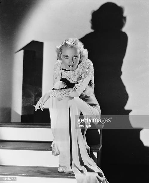 American film actress Carole Lombard casts a dramatic shadow against the wall behind her
