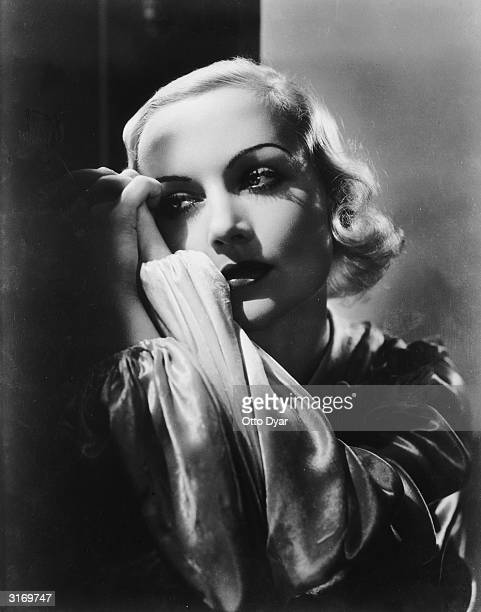 American film actress Carole Lombard clasps her hands together as if in prayer