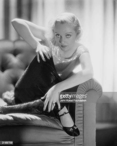 American film actress Carole Lombard curls up on an armchair