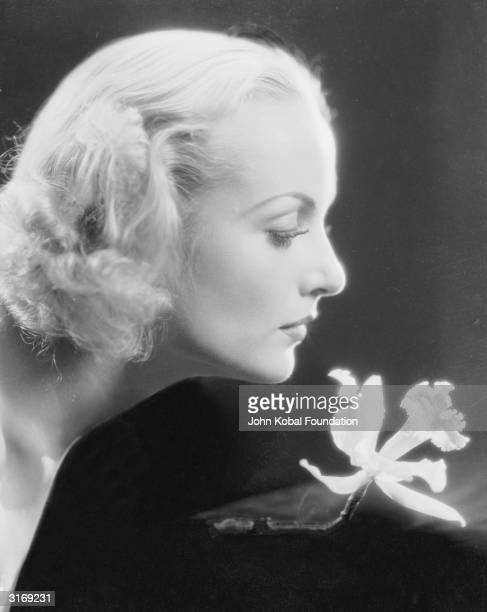American film actress Carole Lombard leans forward to sniff an orchid