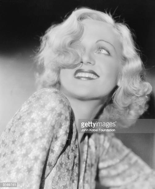 American film actress Carole Lombard lets a curl of hair fall over one eye