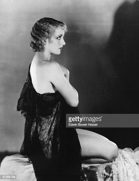 American film actress Carole Lombard lets her dress slip off one shoulder