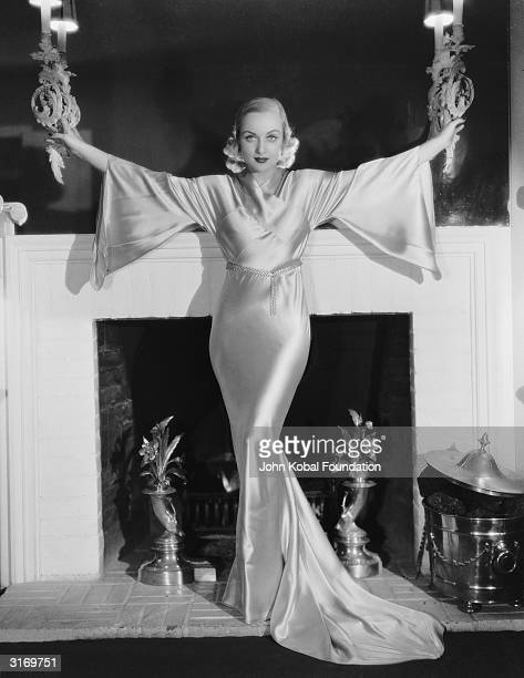 American film actress Carole Lombard poses in front of a mantelpiece in a dramatic silk gown