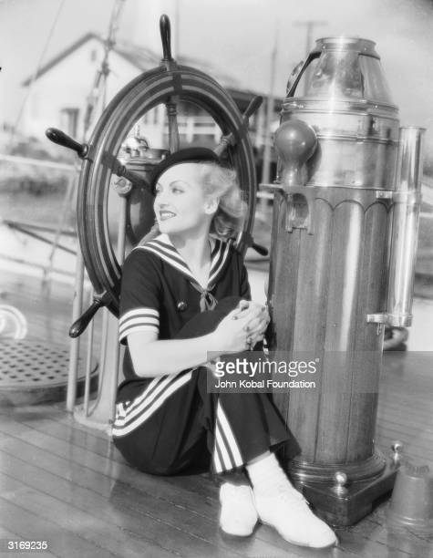 American film actress Carole Lombard posing next to a ship's wheel in a sailor suit