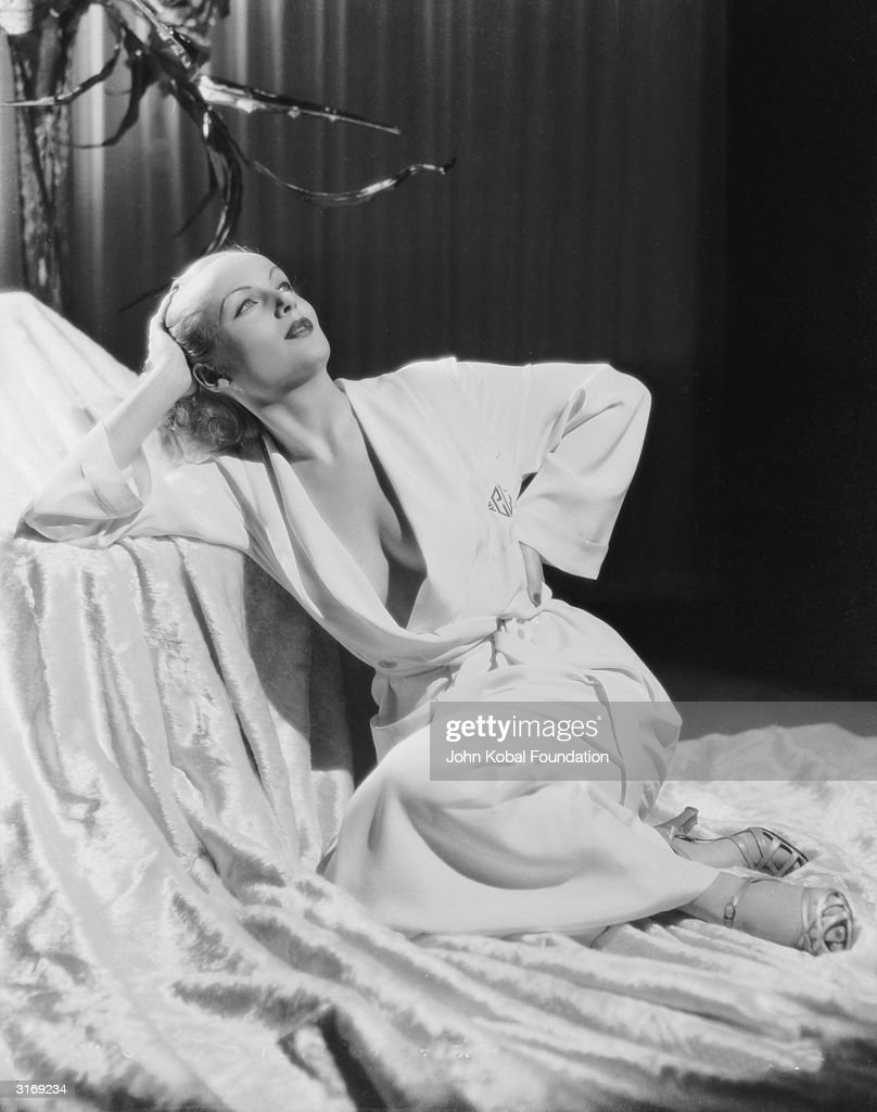 American film actress Carole Lombard (1908 - 1942) wearing a daringly loose dressing gown to show an expanse of cleavage.