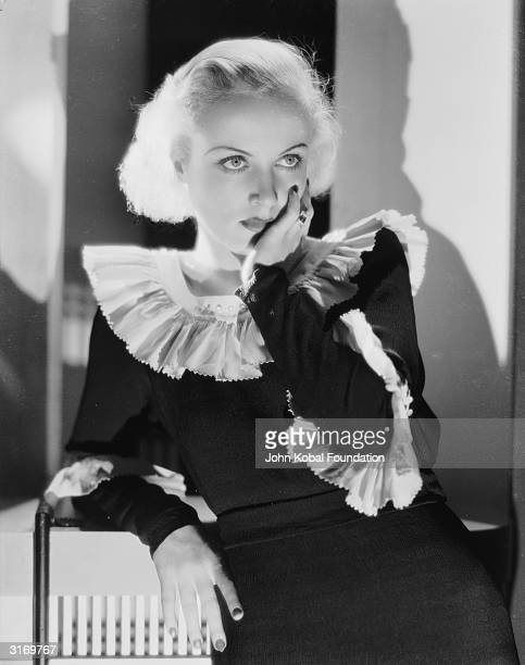 American film actress Carole Lombard wearing a dark dress with a frilled collar and cuffs