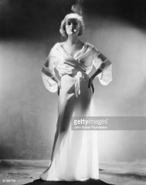 American film actress Carole Lombard wearing a diaphanous belted gown