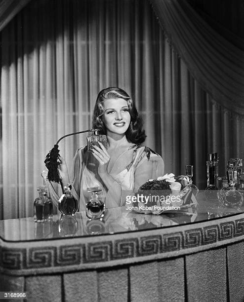 American film actress, dancer and singer Rita Hayworth sprays herself with perfume at a dressing table.