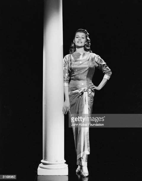 American film actress dancer and singer Rita Hayworth wearing a metallic gown and leaning against a pillar