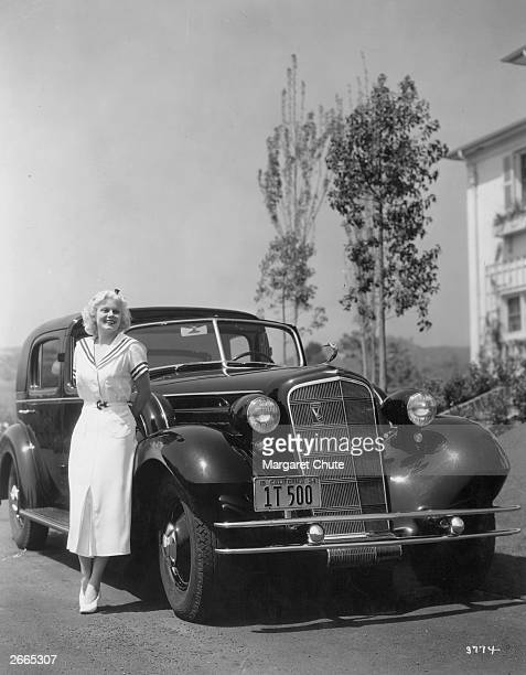 American film actress Jean Harlow poses with her new Cadillac V12 motor car